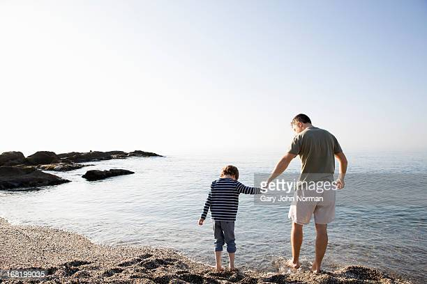 dad and son paddling in sea