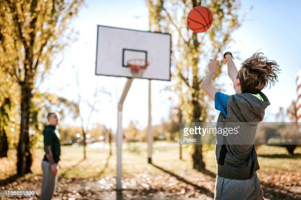 dad and son playing basketball outdoor - hitting stock pictures, royalty-free photos & images