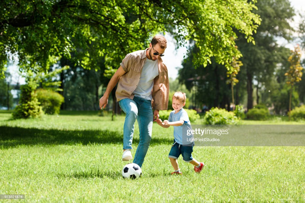 dad and son playing football at park : Stock Photo
