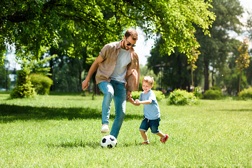 dad and son playing football at park 973321378
