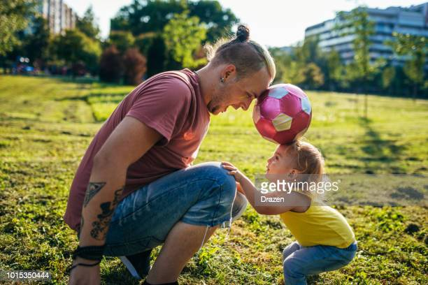 dad and son playing soccer - football bulge stock photos and pictures