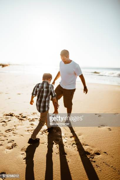 dad and son playing together at soccer on the beach - kicking stock pictures, royalty-free photos & images