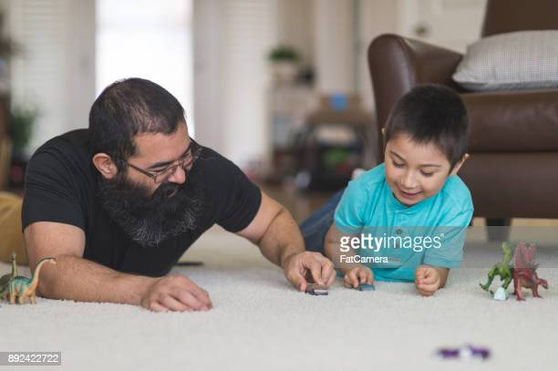 dad and son playing with toy cars on the floor - mixed wrestling stock pictures, royalty-free photos & images