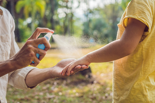 dad and son use mosquito spray.Spraying insect repellent on skin outdoor 992623654