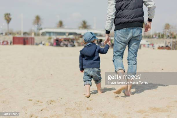 Dad and son walking in the beach
