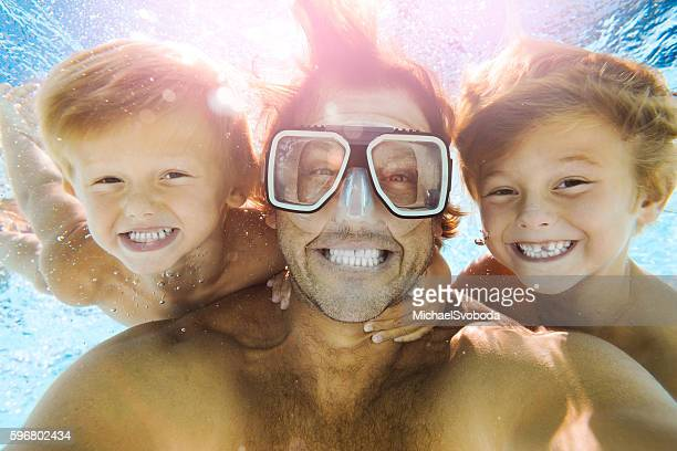 dad and sons having fun doing a selfie underwater - family with two children stock photos and pictures