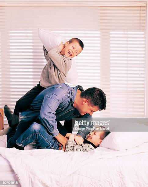 Dad and sons having pillow fight