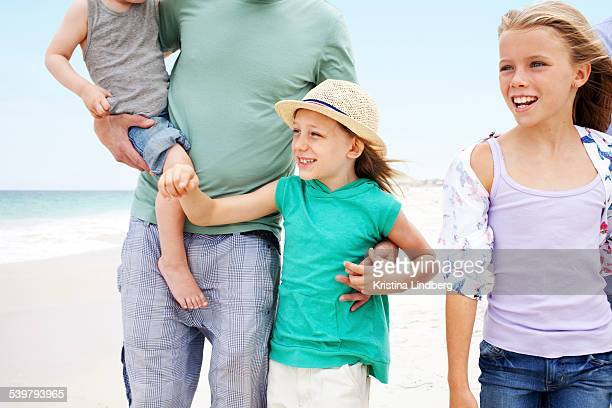 Dad and three kids walking on beach