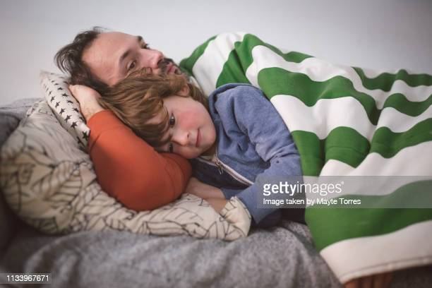 Dad and toddler trying to have a nap in the sofa