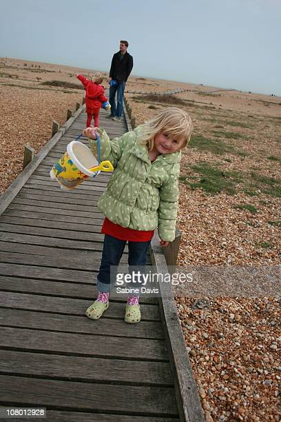 Dad and twin daughters on the beach at Dungeness