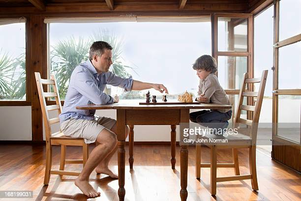 Dad and young son playing chess