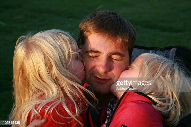 dad being kissed by twin daughters