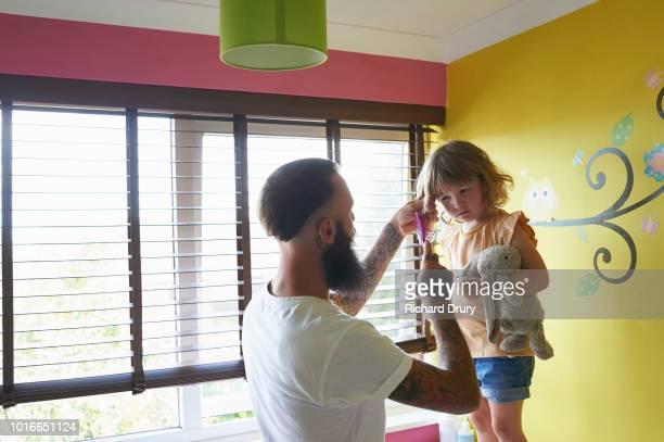 Dad brushing daughters hair in bedroom