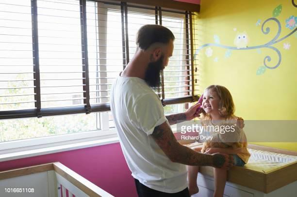 Dad brushing toddler daughter's hair