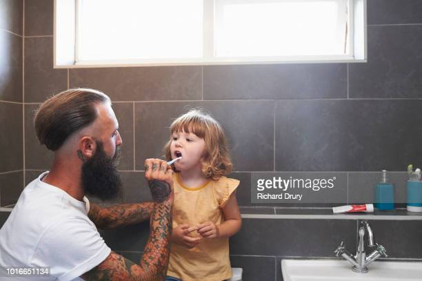dad brushing toddler daughter's teeth - cuidado com o corpo - fotografias e filmes do acervo