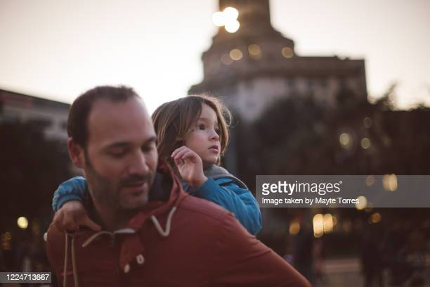 dad carrying boy on his back in the city while he looks away - 脱・男らしさ ストックフォトと画像