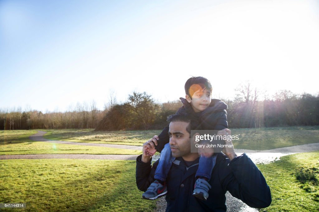 Dad carrying young son on shoulders : Stock Photo