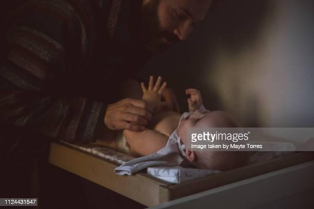 dad changing diaper to baby boy - オムツを替える ストックフォトと画像