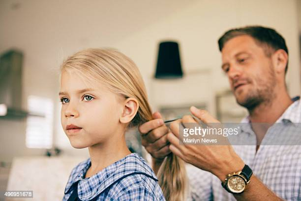 dad combing daughters hair in the morning