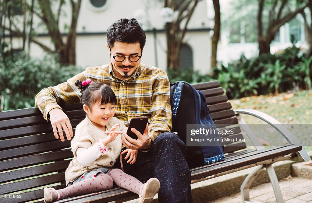 dad daughter using smartphone in park ストックフォト getty images