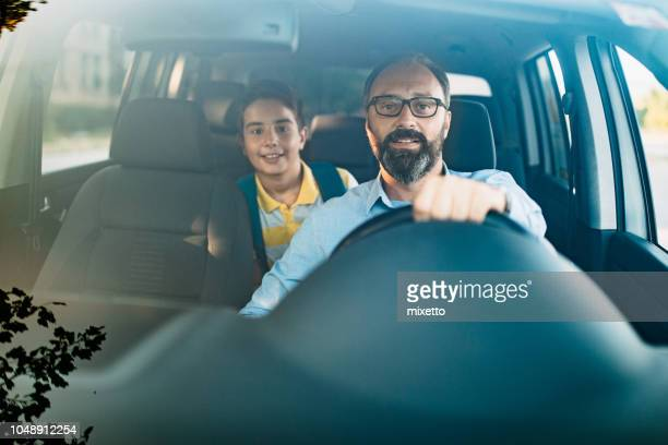 vader rijdt zoon op school - frontaal stockfoto's en -beelden