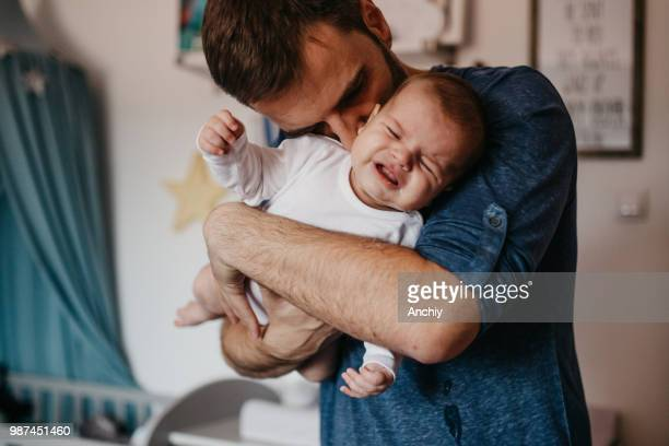 Dad embracing crying baby