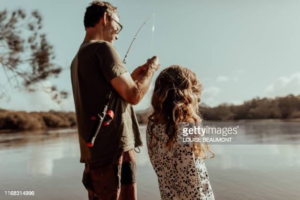 dad fixes fishing rod for his daughter - simple living stock pictures, royalty-free photos & images
