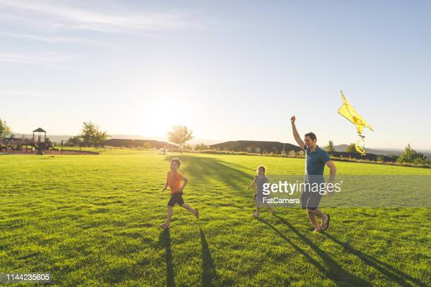 dad flying kites with his kids at the park - public park stock pictures, royalty-free photos & images