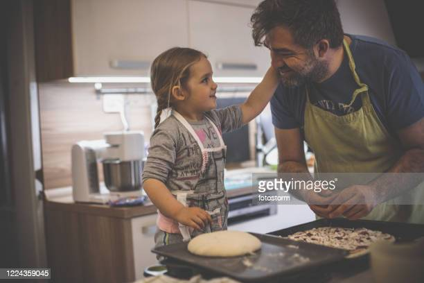 dad gets congratulated by daughter while cooking pizza - i love you stock pictures, royalty-free photos & images