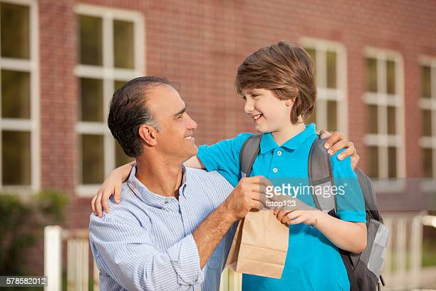Dad gives lunch sack to boy.  First day of school.