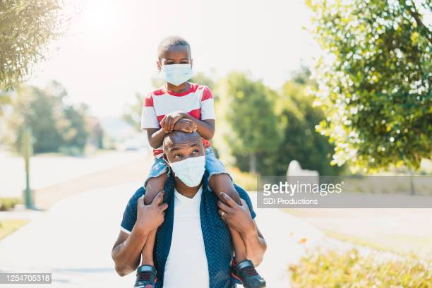 dad gives son piggy back ride; both wear masks - family politics stock pictures, royalty-free photos & images