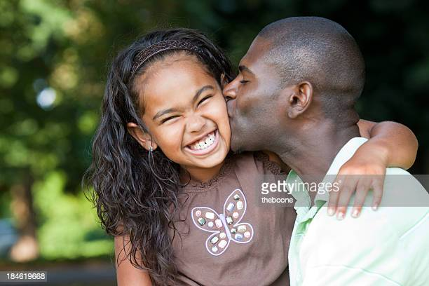 dad giving his daughter a kiss on the cheek