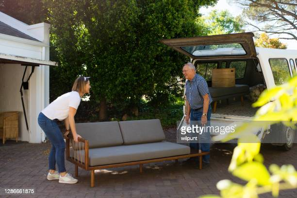 dad helping daughter move couch from a truck outdoors - luton stock pictures, royalty-free photos & images