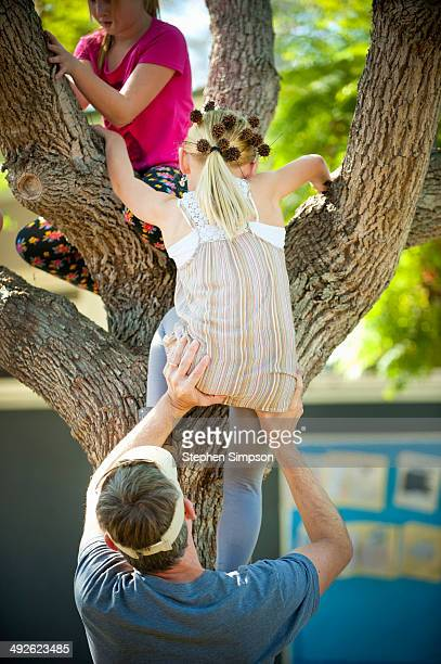 dad helping girls climb a tree - little girls bare bum stock pictures, royalty-free photos & images