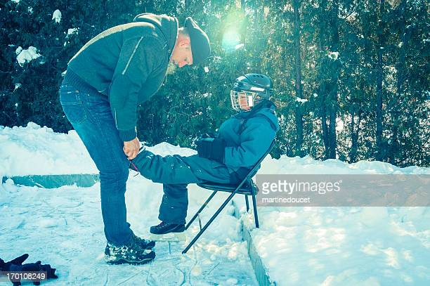Dad helping son tying his skates outside with sun flare.