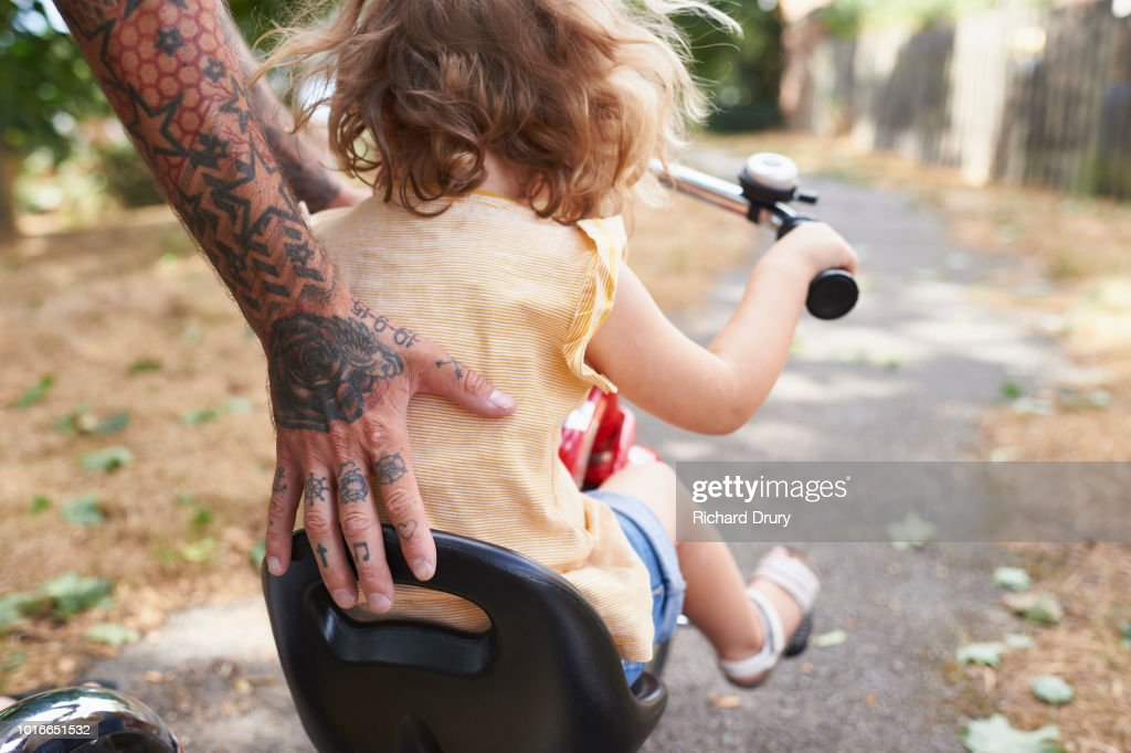 Dad helping toddler daughter to ride her tricycle : Foto de stock