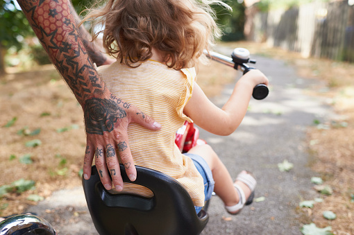 Dad helping toddler daughter to ride her tricycle - gettyimageskorea