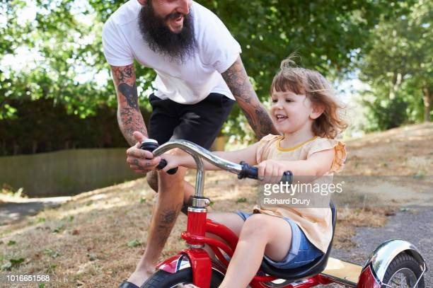 dad helping toddler daughter to ride her tricycle - beginnings stock pictures, royalty-free photos & images