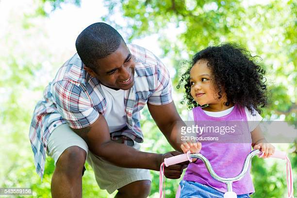 Dad helps his daughter ride tricycle in the park
