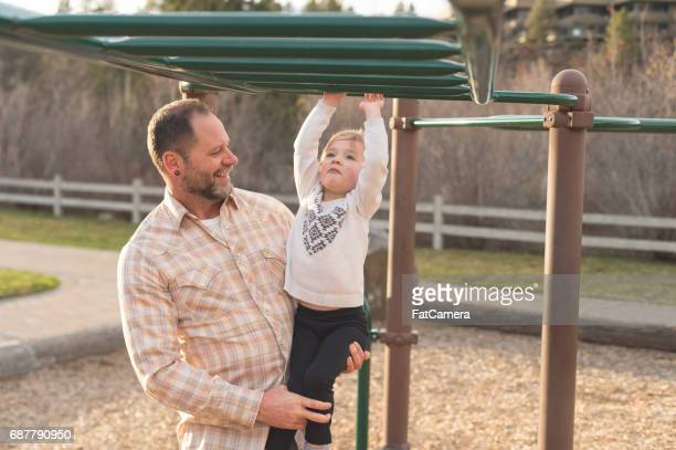 Dad helps his young daughter learn to use the monkeybars at the playground