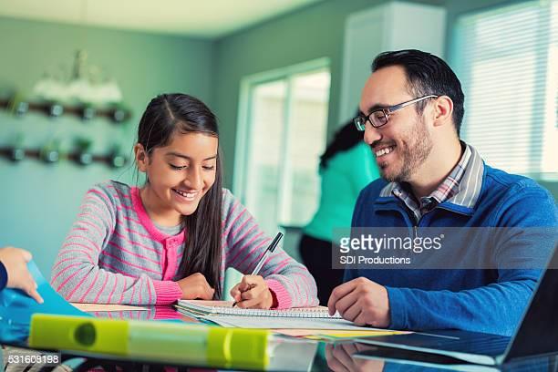 Dad helps pre-teen daughter with school assignment