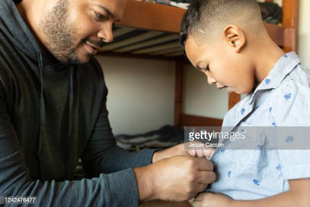 dad helps son to button up shirt - child in bed clothed stock pictures, royalty-free photos & images