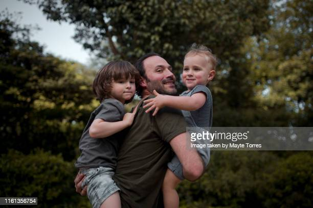 dad holding both children - modern manhood stock pictures, royalty-free photos & images