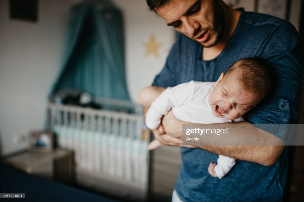 Dad Holding crying baby in the colic carry : Stock Photo