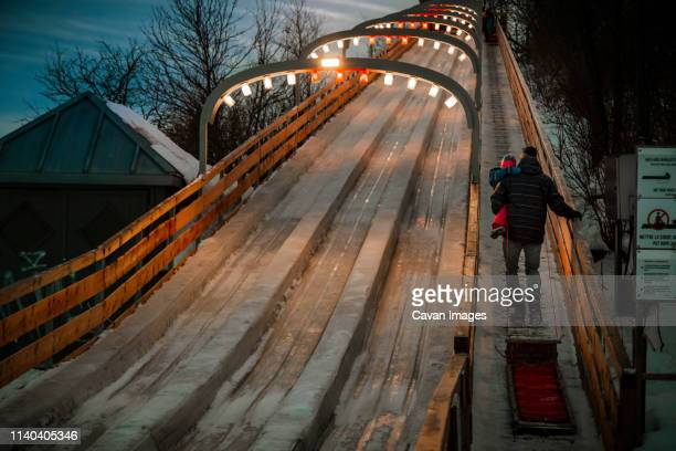 dad holding his daughter in his arms at icy toboggan at winter dusk - tobogganing stock pictures, royalty-free photos & images