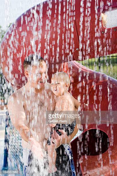 Dad holding son under shower of water drops