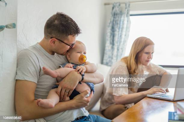 dad holds baby daughter so mom can work on her computer - stereotypical stock pictures, royalty-free photos & images