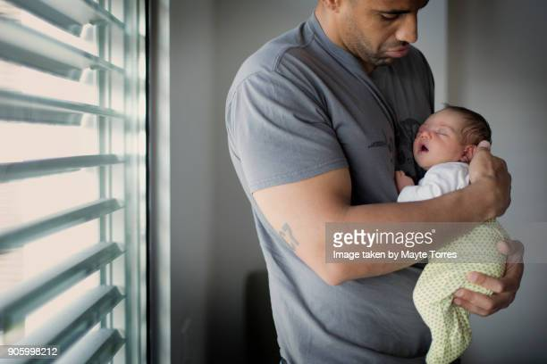 dad holds newborn daughter staing next to a window - black man holding baby stock photos and pictures