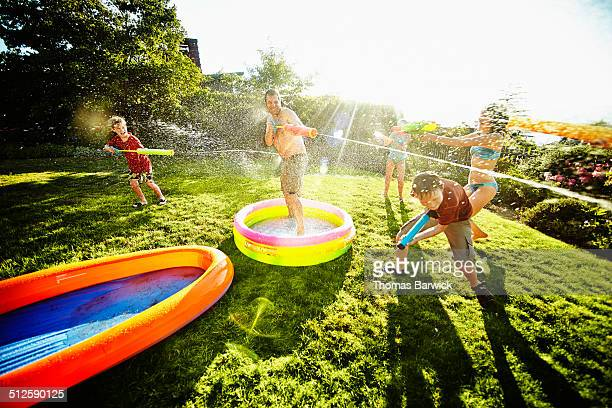 Dad in water fight with kids in backyard