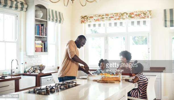 dad is cooking up a storm for the family - african american family home stock photos and pictures